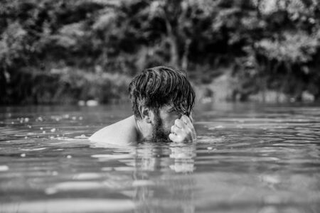 Deep dangerous water. Submerge into water. Freshness of wild nature. Summer vacation. Relaxation and rest. Swimming sport. Swimming skills. Refreshing feeling. Man enjoy swimming in river or lake.