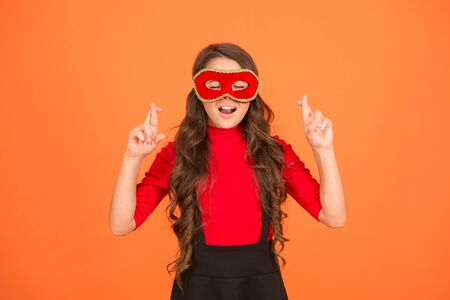 Cross fingers. Cute child make wish orange background. Little child keep fingers crossed for luck. Small child with long hair wear carnival mask. Party child. Childhood dream. Turn away the evil eye.