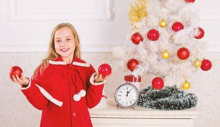 Child red costume hold christmas ornament ball. Christmas ball traditional decor. Top christmas decorating ideas for kids room. Kids can brighten up christmas tree by creating their own ornaments