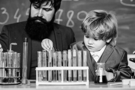 Chemistry and physics biology. father and son at school. bearded man teacher with little boy. Back to school. Explaining biology to child. biotechnoloy research concept. Got my ion you