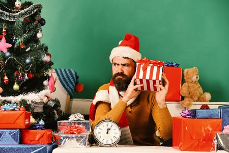 Santa holds gift box. Man with beard and curious face