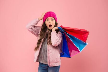 Bags perfect for carrying all epic shopping. Shocked shopper hold shopping bags. Little child with paper bags. Small girl carry holiday purchases in colorful bags. Autumn sale and discount Stock Photo