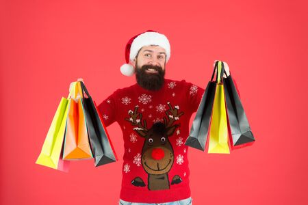 Christmas gifts. Presents for family. Santa is coming. Bearded hipster carry shopping bags. Packages with gifts. Happy man bought gifts. Spending more than you planned initially. Shopaholic concept