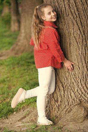 She is really cute. Fashion little lady. Fashionable child in casual fashion style at tree. Adorable girl of fashion in casual wear on summer day. Fashion look of small vogue model