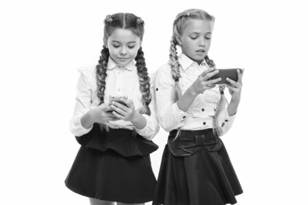 Generation of mobile communication. Little pupils using mobile devices isolated on white. Small schoolchildren having e-lesson on mobile phones. M-learning or mobile learning