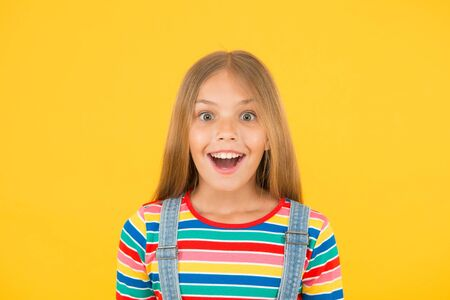 Happy childrens day. childhood happiness. cheerful hipster girl colorful clothes. optimist concept. small girl yellow background. summer kid fashion. kid positive mood. Child happiness portrait