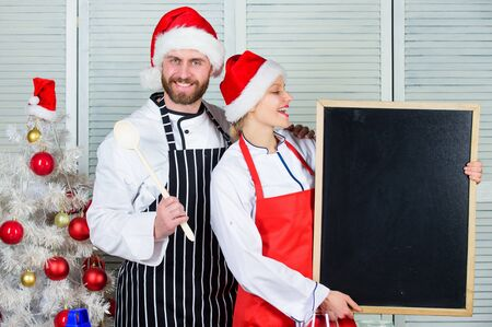 Man and woman chef santa hat near christmas tree. Christmas recipe concept. Couple preparing healthy vegetarian meal together for christmas dinner. Secret ingredient is love. Cooking christmas meal
