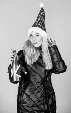 Feast of Christmas. woman down jacket hold champagne. girl santa claus hat. warm clothing. fun and gifts. happy new year. merry christmas celebration. xmas toast. winter holidays and vacation