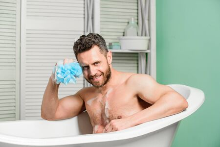 macho man washing in bath. desire and temptation. hygiene and health. Morning shower. man wash muscular body with foam sponge. personal care. Sexy man in bathroom. spa and beauty concept Banco de Imagens