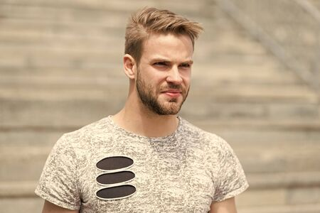 Handsome and attractive. Handsome man in summer style on sunny day. Caucasian guy with beard on unshaven handsome face and stylish blond hair on urban outdoor. Casual and handsome