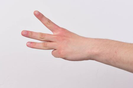 Count down and numbers concept. Male hand shows three fingers. Hand gesture expresses numbers. Hand isolated on light grey background, copy space.
