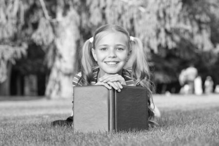 School time. Developing caring learners who are actively growing and achieving. Little child reading book. Adorable bookworm. Schoolgirl reading stories relaxing green lawn. Cute pupil enjoy reading