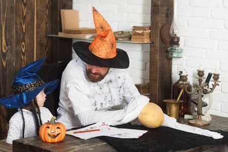 Hexer und kleiner Zauberer machen Dekoration für Halloween. Mann und Kind in Hexenhüten schauen sich an und spielen mit Kürbissen. Halloween- und Partykonzept. Kerl und Junge auf Holz und weißem Backsteinhintergrund
