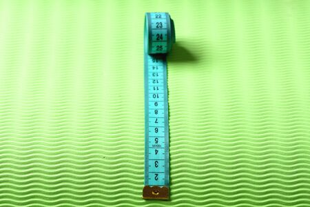 Measuring tape roll in cyan color on green texture background. Sports and healthy lifestyle concept. Shaping and fitness equipment, close up. Flexible ruler in blue lying on yoga mat, selective focus
