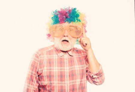 Nice joke. Elderly clown. Man senior bearded cheerful person wear colorful wig and sunglasses. Grandpa always fun. Having fun. Funny lifestyle. Fun and entertainment. Comic grandfather concept