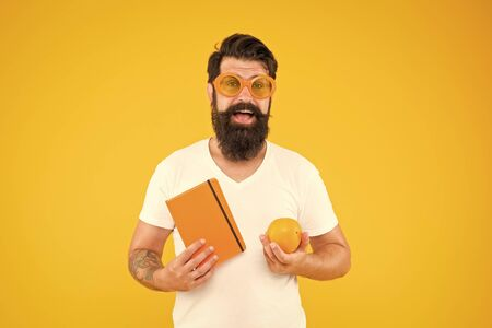 Being proud of geek in you. Geek man. Bearded man in geek glasses holding orange and book on yellow background. Hipster in geek chic style choosing healthy food for brain