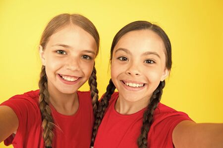 Say cheese. Child girls taking photo. Children kids happy faces. Video call concept. Video conference camera. Girls long hair taking selfie. Selfie for social networks. Brilliant toothy smile Stock Photo