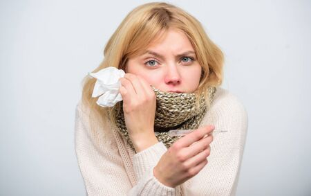 Girl sick hold thermometer and tissue. Measure temperature. Break fever remedies. Seasonal flu concept. Woman feels badly. How to bring fever down. Fever symptoms and causes. Sick girl with fever Фото со стока