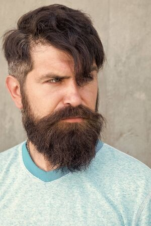 My hair speaks for itself. Serious guy wearing shaped beard and styled hair. Hairy hipster with stylish beard and mustache hair on grey wall. Bearded man with unshaven face hair and trendy haircut