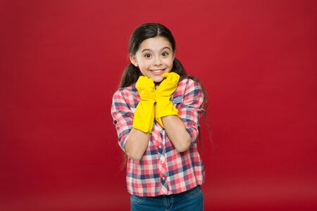 Appreciate cleanliness. Clean house. Housekeeping duties. Inspiring changes. Spring cleaning. House cleaning service. Cleaning supplies. Small girl rubber gloves for cleaning red background Reklamní fotografie