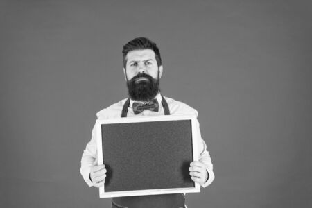 urgent to eat. Food blogger. serious hipster bartender. What to cook. Restaurant menu. cafe shop advertisement. bearded man chalkboard, copy space. brutal waiter in kitchen. mature man red background
