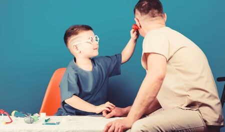 Hospital worker. Health care. Medicine concept. Kid little doctor sit table medical tools. Illness treatment. Dad and son medical dynasty. Medical examination. Boy cute child and his father doctor Stock fotó