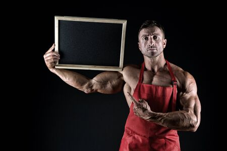 and muscular chef show blackboard. copy space. athletic bodybuilder in cook apron. housekeeper pointing finger on board. place for your advertisement. healthy menu here. beat food and coffee