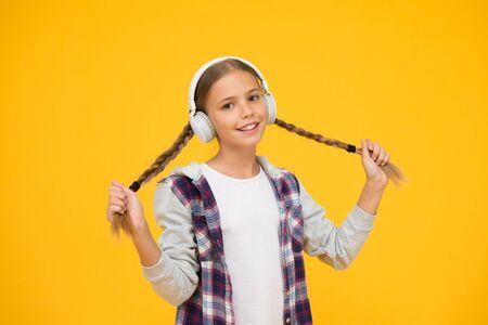 Headphones with wireless technology. Small child listening to music modern wireless earphones. Happy little girl wearing modern headphones. Cute kid enjoying stereo sound. Wireless means freedom