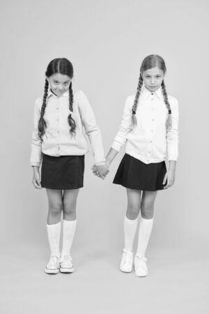 Schoolgirls best friends excellent pupils. Schoolgirls tidy appearance school uniform. School friendship. September again. Childhood happiness. School day fun cheerful moments. Kids cute students