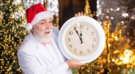 Merry Christmas. new year midnight. clock showing almost midnight. time to celebrate winter holidays. hurry up. Christmas countdown arriving. wait for xmas presents. santa man hold alarm clock
