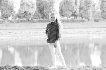 A typical day in childhood. Happy little girl wearing casual clothes for vacation at riverside. Childhood activities on summer day. Happy childhood. Childhood and growing up