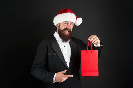 Product you should buy over Christmas holiday. Bearded man presenting product. Happy boss point finger at shopping bag. Product promotion. Christmas sale. Product advertising, copy space