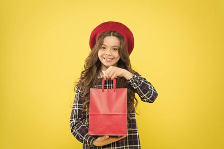 Easy to use bag. Happy girl holding shopping bag on yellow background. Little child smiling with paper bag after fashion sale. Small kid carrying purchase in red non grocery carrier bag