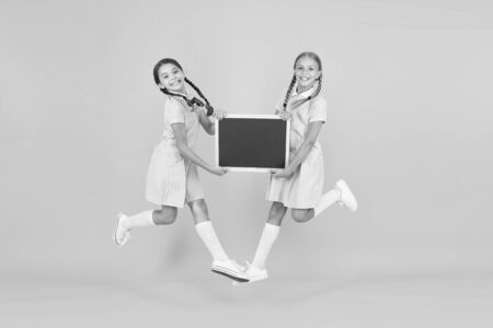 real happiness. small girls jump with blackboard. children education. small girls presenting info. old school. copy space on board. happy friends in retro uniform. vintage kid fashion. back to school