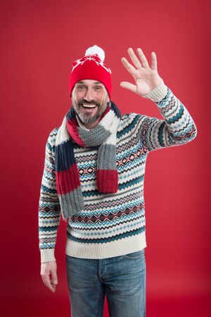 Winter knitwear. Knitwear accessories. Mature man red background. Bearded man in winter style. Caucasian man wear warm clothes. Fashion and style. Winter trends. Knitted hat scarf and sweater