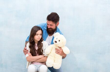Look at this toy. Father show soft toy to little daughter. Upset child and bearded man with toy bear. Game and play. Toy shop. Stay childish, copy space Foto de archivo
