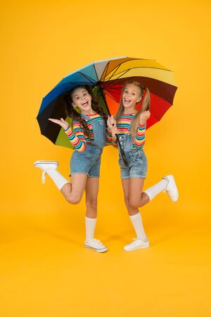 Perfect place to stay. small girl under colorful umbrella. two happy kids yellow background. children enjoy rainy autumn. fall kid fashion. feeling safe and comfortable. Good mood at any weather
