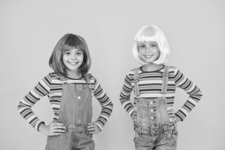 Life is better with friends. Happy girls friends on yellow background. Little friends smile in fashionable hair wigs and stylish overalls. Adorable small friends enjoy friendship. Playmates