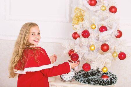 Laissez l'enfant décorer le sapin de Noël. Décoration de partie préférée. Faire participer l'enfant à la décoration. Fille cheveux longs tenir boules ornements fond intérieur blanc. Comment décorer le sapin de Noël avec un enfant Banque d'images