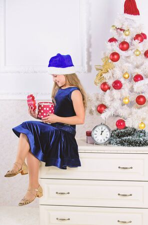 Little girl santa hat excited about christmas gift or present. Time to open christmas gifts. Happy new year concept. Child celebrate christmas at home. Kid girl sit near christmas tree hold gift box