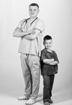 little boy with dad in hospital. happy child with father with stethoscope. family doctor. medicine and health. father and son in medical uniform. Everything must be perfect. using stethoscope