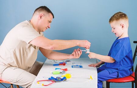 Man doctor sit table medical tools examining little boy patient. Pediatrician concept. Health care. Child care. Careful pediatrician check health of kid. Medical examination. Medical service Stock Photo - 136797460