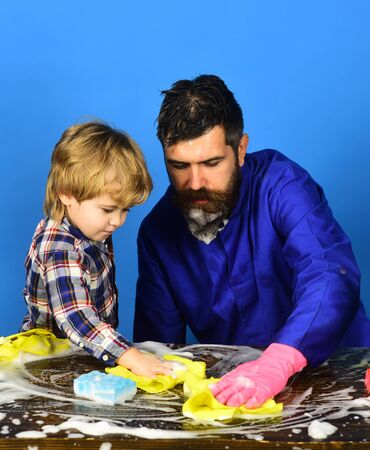 Man and child cleaning table with rags and foam.