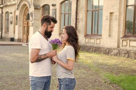Couple meeting for date. Bouquet gift. Man giving flower bouquet. Romantic date. Guy prepared surprise bouquet for girlfriend. True feelings. Pick up girl for date. Bearded hipster fall in love