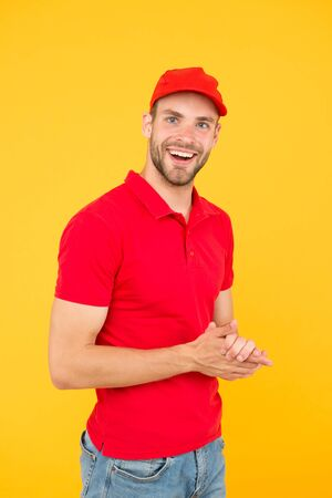 Postman delivery worker. Man red cap yellow background. Delivering purchase. Already ready. Easing your business. Service delivery. Salesman and courier career. Courier and delivery service