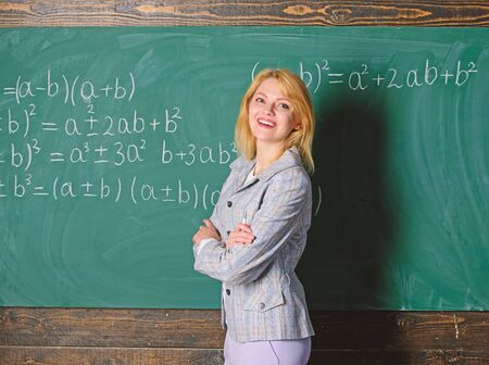 Working conditions which prospective teachers must consider. Working conditions for teachers. She likes her job. Back to school concept. Woman smiling educator classroom chalkboard background