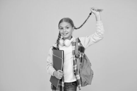 Long and braided. Cute small schoolchild hold long hair braid on yellow background. Adorable little girl wear long hair style. Styling long hair for school Reklamní fotografie