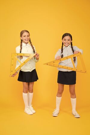 Kids cute students study math. Knowledge day. Move from theory to practice. Excellent pupils. Secondary school. Schoolgirls tidy appearance school uniform hold big rulers for geometry school lesson