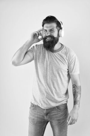 Because Im happy. Happy hipster listen to music yellow background. Bearded man enjoy song playing in headphones. Happy and upbeat melody. Music makes him feel happy