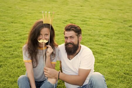 Shes a big boss here. Couple in love sitting on green grass. Pretty girl wearing prop crown and boss mustache. Proud girl feeling like a boss next to boyfriend. Big boss and pride